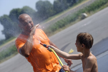 Boy splashing water on his father with garden hose - LBF001324