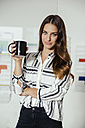 Young woman standing in office, holding a coffe mug - MFF002547