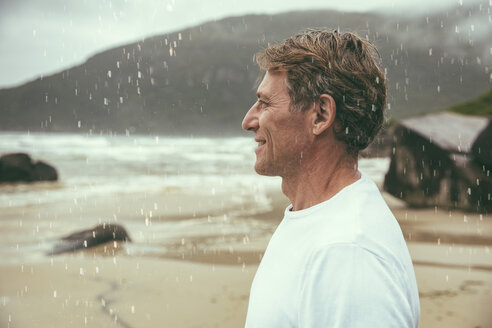 Brazil, Florianopolis, profile of happy man standing in the rain on the beach - MFF002568