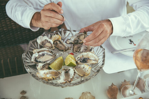 Hands of a man eating fresh oysters in a restaurant - MFF002571