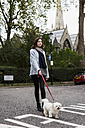 UK, London, young woman going walkies with her dog - MAUF000178