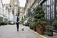 UK, London, young woman going walkies with her dog - MAUF000184