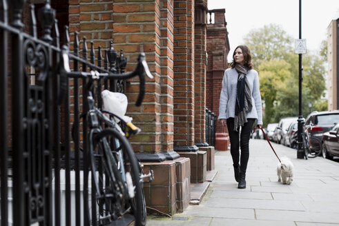 UK, London, young woman going walkies with her dog - MAUF000190