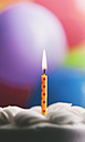 Lighted birthday candle on a cake in front of balloons - SELF000084