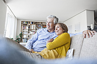 Smiling couple relaxing on the couch at home - RBF003749