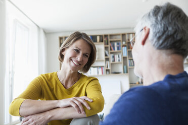 Portrait of smiling womanface to face with her husband in the living room - RBF003755