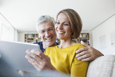 Smiling couple sitting on the couch at home using digital tablet - RBF003758