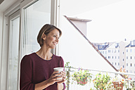 Smiling woman leaning against balcony door looking at distance - RBF003770