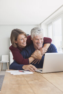 Happy couple using laptop at home - RBF003788