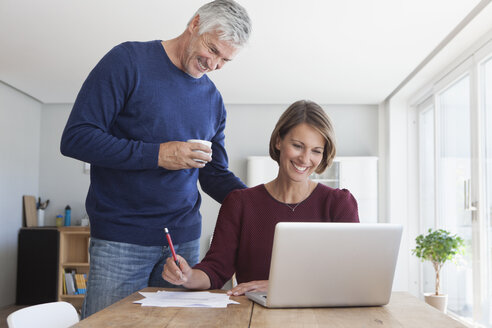 Happy couple with laptop at home - RBF003791