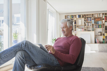 Mature man relaxing on leather chair at home using digital tablet - RBF003797