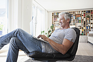 Smiling man relaxing on leather chair at home using laptop - RBF003800