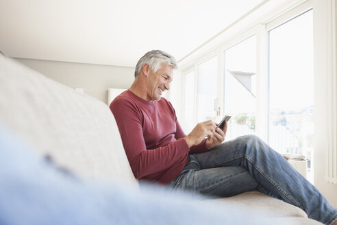 Smiling man sitting on the couch at home using smartphone - RBF003809