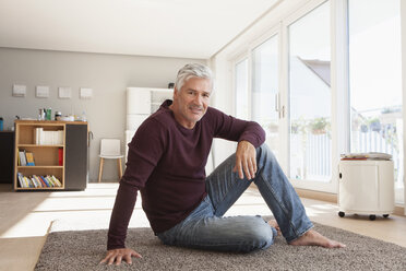 Portrait of mature man sitting on the floor at home - RBF003818