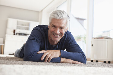 Portrait of smiling man lying on the floor at home - RBF003824