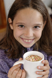 Portrait of happy girl holding cup of hot chocolate with marshmallows - LBF001329