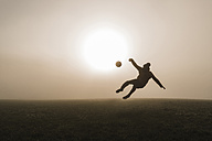 Young man playing soccer on meadow in the evening - UUF006219