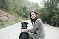 Portrait of smiling woman with her dog in nature - GEMF000577