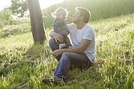 Father playing with his little daughter on a meadow - PAF001515