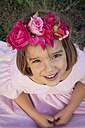 Portrait of smiling little girl wearing flowers looking up to camera - LVF004333