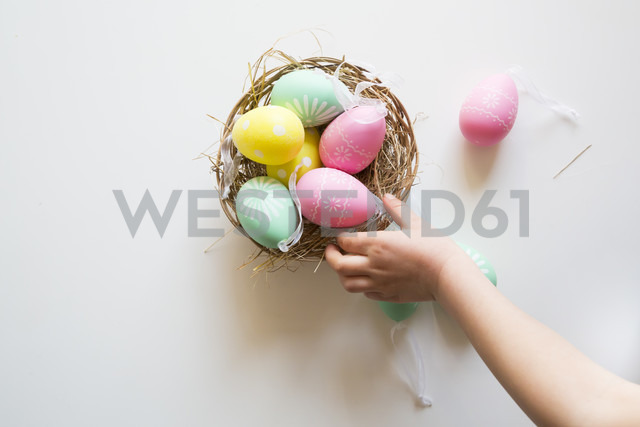 Little girl's hand taking coloured Easter egg - LVF004339