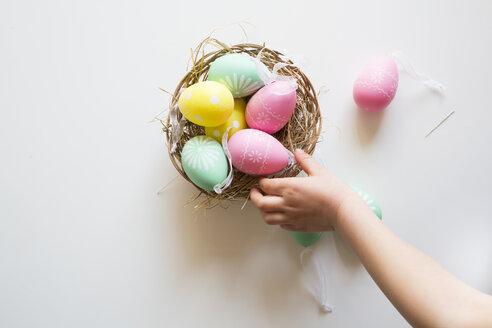 Little girl's hand taking coloured Easter egg - LVF004339