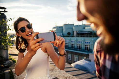 Austria, Vienna, portrait of smiling young woman taking a photo of her boyfriend on a roof terrace - AIF000131