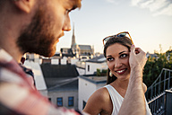 Austria, Vienna, portrait of smiling young woman face to face with her boyfriend on a roof terrace - AIF000134