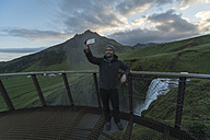 Iceland, Man taking selfie at Skogafoss waterfall - PAF001521