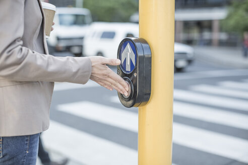 Woman waiting to cross a city street, pressing pedestrian crossing button - ZEF007774