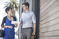 Colleagues discussing in the street, woman holding tablet pc - ZEF007795