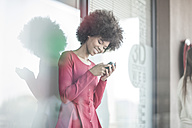 Young woman reading messages on smart phone - ZEF007804