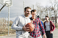 Young man with basketball and friends on basketball court - UUF006279