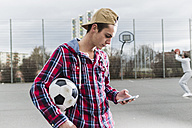Young football player with smartphone - UUF006300