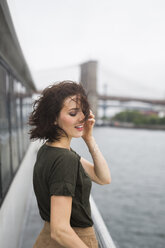 USA, New York City, young woman standing on an excursion boat on a windy day - GIOF000608