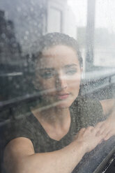 Portrait of young woman looking through window of an excursion boat on a rainy day - GIOF000611