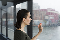 Young woman looking through window of an excursion boat on a rainy day - GIOF000617