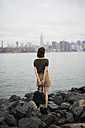 USA, New York City, back view of young woman looking to Manhattan skyline from Williamsburg bank - GIOF000620