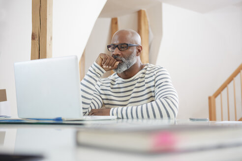 Portrait of man sitting at desk of  home office looking at his laptop - RHF001152