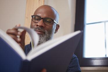 Portrait of man reading a book - RHF001155