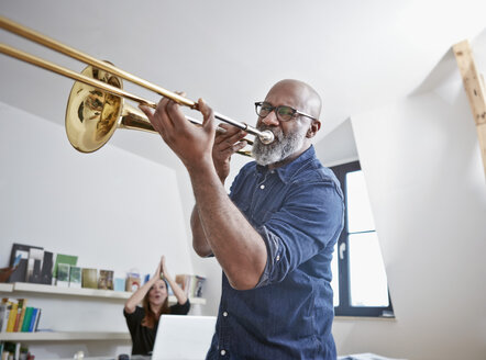 Portrait of man playing trombone at home office - RHF001158