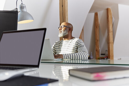 Man with closed eyes sitting at his desk relaxing - RHF001191