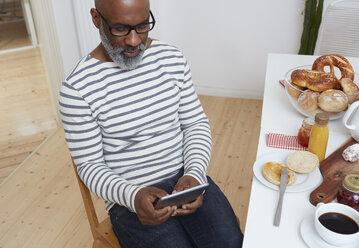 Man sitting at laid breakfast table using digital tablet - RHF001200