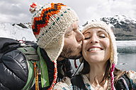 Peru, couple wearing wool chullos and kissing - GEMF000585