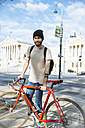 Young man with racing cycle in Vienna, in front of parlament building, Dr.-Karl-Renner-Ring - AIF000141