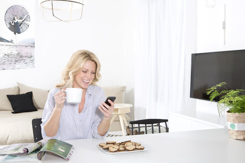 Smiling woman sitting at the table in her living room holding coffee cup while looking at smartphone - MAEF011221