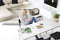 Smiling woman sitting at the table in her living room using digital tablet - MAEF011224