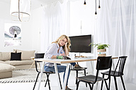 Woman sitting at the table in her living room with magazine - MAEF011227