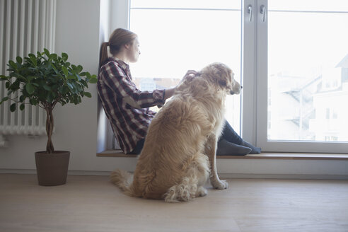 Young woman stroking her dog while looking through the window - RBF003832