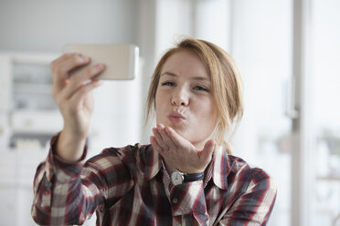Young woman blowing a kiss while taking a selfie with her smartphone - RBF003841
